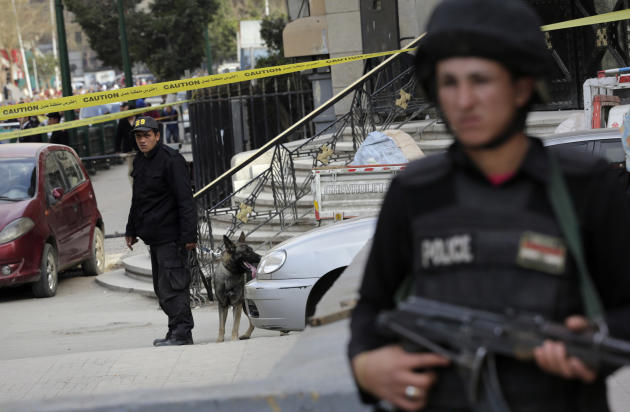 An Egyptian policeman stands alert as another member of bomb squad handle a sniffer dog after a bomb blast near the Egyptian High Court, in downtown Cairo, Egypt, Monday, March 2, 2015. Egyptian state