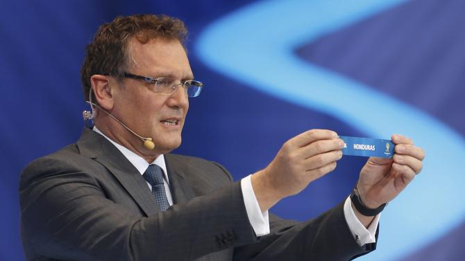 """Valcke holds up the slip showing """"Honduras"""" during the draw for the 2014 World Cup in Sao Joao da Mata"""