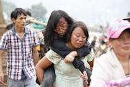 A woman (C) carries an injured girl following the earthquake in Ludian county in Zhaotong, southwest China's Yunnan province on August 4, 2014
