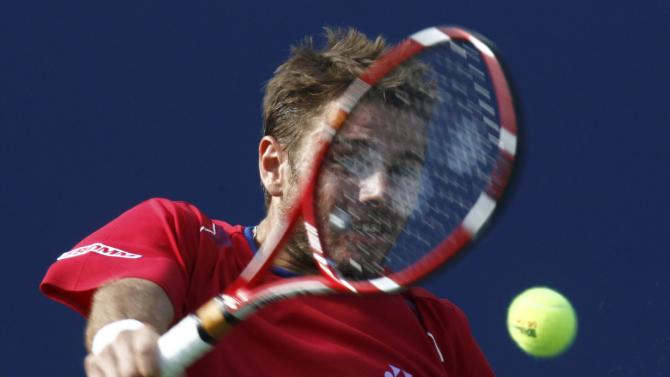 Wawrinka of Switzerland hits a return to Djokovic of Serbia during their men's semi-final match at the U.S. Open tennis championships in New York