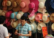 A vendor sells hats on a shopping street in Shanghai on July 9, 2012. Retail sales, the main gauge of consumer spending in China, continued to slow in June