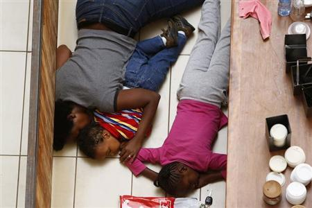A mother and her children hide from gunmen at Westgate Shopping Centre in Nairobi September 21, 2013. Gunmen stormed the shopping mall in Nairobi on Saturday killing at least 20 people in what Kenya's government said could be a terrorist attack, and sending scores fleeing into shops, a cinema and onto the streets in search of safety. Sporadic gun shots could be heard hours after the assault started as soldiers surrounded the mall and police and soldiers combed the building, hunting down the attackers shop by shop. REUTERS/Siegfried Modola