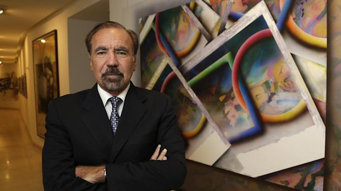 FILE- In this In this Dec. 11, 2013 file photo, developer and art collector Jorge Perez, poses for a photograph in his office at the Related Group, in Miami. Perez is one of Florida's powerful Cuban-American business leaders. He wants to soften the U.S. government's longtime economic embargo against Cuba's communist government. (AP Photo/Lynne Sladky, File)