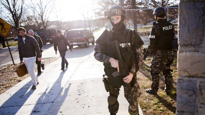 Some students and staff leave as police secure the perimeter of the Virginia Tech campus in Blacksburg, Va. after a gunman walked into a parking lot and killed a Virginia Tech police officer who was conducting a traffic stop, Thursday, Dec. 8, 2011. Another person, a white man, died of a gunshot wound in a different parking lot. (AP Photo/The Roanoke Times, Sam Dean)