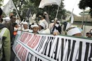 """Islamic hardliners protest outside the Myanmar embassy in the Indonesian capital Jakarta on Friday to """"stop the genocide"""" of Rohingya Muslims in the wake of deadly communal unrest. Around 300 hardliners from organisations, including the Islamic Defenders Front (FPI) and Jemaah Anshorut Tauhid (JAT), threatened to storm the Myanmar embassy in Jakarta as some 50 police officers guarded the building"""