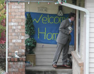 """A reporter knocks on the door where a """"welcome home"""" sign is posted at the home of Curt Knox for his daughter Amanda Knox on her expected arrival later in the day Tuesday, Oct. 4, 2011, in Seattle. It's been four years since the University of Washington student left for the study abroad program in Perugia and landed in prison. The group Friends of Amanda Knox and others have been awaiting her return since an Italian appeals court on Monday overturned her conviction of sexually assaulting and killing her British roommate. (AP Photo/Elaine Thompson)"""