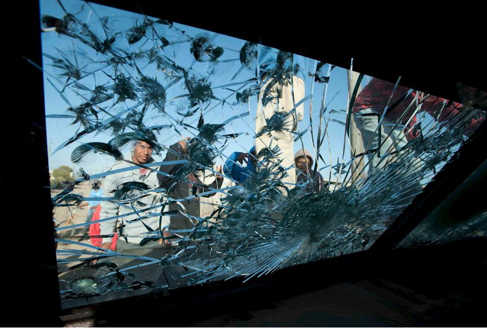 Protesters are seen through the broken windshield of a vandalised police vehicle after a confrontation between police and day labourers in the town of San Quintin in Baja California