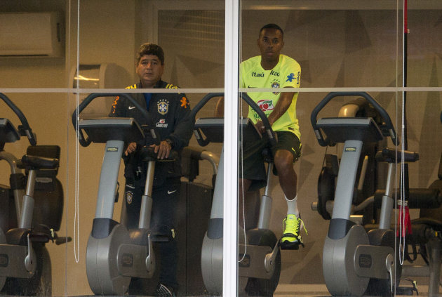 Brazil's soccer player Robinho, right, rides a stationary bike after pulling out of his team's training session due to a knee problem, in Teresopolis, Brazil, Friday, June 5, 2015. Brazil is training for the Copa America which starts this month in Chile. (AP Photo/Silvia Izquierdo)