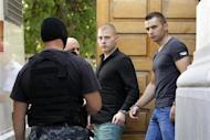 Eugen Darie (C) and Radu Dogaru (R), suspects charged with stealing paintings from a Dutch museum, are escorted by police as they leave a court building handcuffed after the first hearing in their trial in Bucharest August 13, 2013. REUTERS/Bogdan Cristel/Files