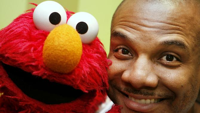 FILE - This Aug 16, 2006 file photo shows Kevin Clash, who was the voice and movements behind Sesame Street's Elmo, posing for a picture with Elmo in New York. Three lawsuits brought by men who said Clash sexually abused them when they were underage were tossed out by a federal judge who said in a decision published Monday, July 1, 2013, that the men waited too long to sue. (AP Photo/Seth Wenig, File)