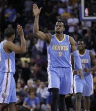 Denver Nuggets' Andre Iguodala (9)celebrates with Andre Miller, left, during double overtime in an NBA basketball game against the Golden State Warriors Saturday, Nov. 10, 2012, in Oakland, Calif. (AP Photo/Ben Margot)