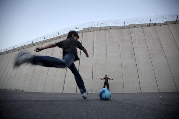 Palestinian children play football in front of the controversial Israeli separation barrier in the West Bank village of Abu Dis, on the outskirts of Jerusalem on November 8, 2012. Israeli and Palestin