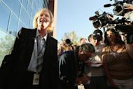 Arapahoe County District Attorney Carol Chambers talks to members of the news media before heading into the Arapahoe County Courthouse in Centennial, Colorado. His hair dyed orange, eyes staring out blankly or drooping shut, presumed Colorado gunman James Holmes seemed unhinged Monday as he made a bizarre first appearance in court
