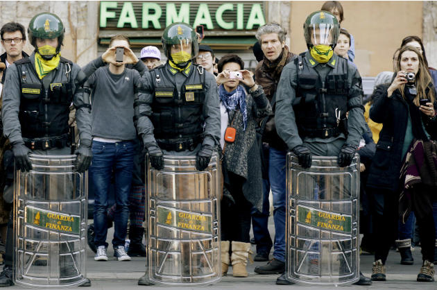 Tourists take pictures flanked by Italian finance policemen in riot gear during a counter-demonstration against Italian Northern League protesters poured simultaneously in Rome and against Italian gov