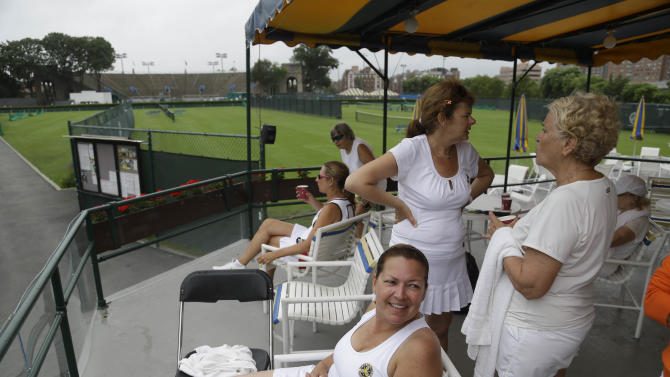 In this Tuesday, July 2, 2013 photo, tennis players relax after matches at the West Side Tennis Club in the Queens section of New York. The Beatles. The Rolling Stones. Frank Sinatra. Jimi Hendrix. Bob Dylan. They've all held court at the more than century-old West Side Tennis Club in Queens' Forest Hills neighborhood - for six decades the site of the U.S. Open Tennis Championships. Plans are now in the works for the grassy lawn to come alive again with the sound of music, starting with a concert featuring the British band Mumford & Sons, to be followed by a lineup of world-class musicians. (AP Photo/Seth Wenig)