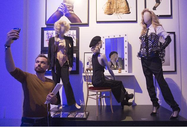 """A visitor takes a photograph with Jean Paul Gaultier creations during a media view of """"The Fashion World of Jean Paul Gaultier, from the Slidewalk to the Catwalk"""" at the Grand Palais  in Par"""