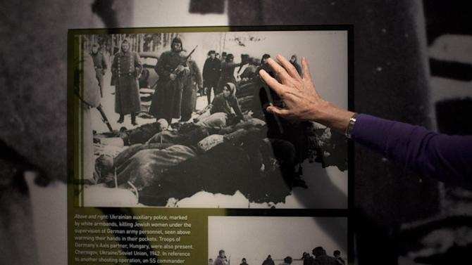 "In this Thursday, April 25, 2013 photo, United States Holocaust Memorial Museum curator Susan Bachrach points out a 1942 photo of Ukrainian auxiliary police killing Jewish women under the supervision of German army personnel and in the presence of Hungarian troops during a preview of the new exhibit ""Some Were Neighbors: Collaboration & Complicity in the Holocaust"" in Washington. The exhibition, opening April 30, 2013, includes interviews with perpetrators of collaboration and complicity in the Nazi genocide. (AP Photo/Carolyn Kaster)"
