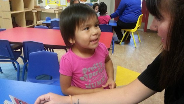 A student approaches her caregiver at a Winnipeg daycare.