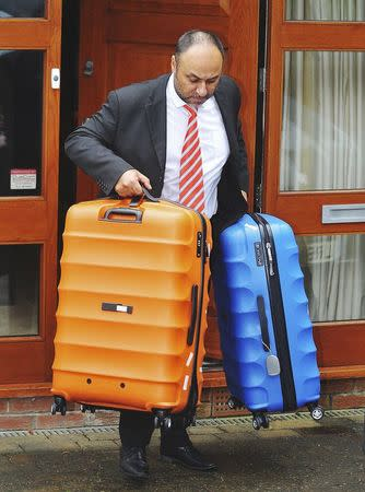A man carries luggage from the home of former England soccer manager Sam Allardyce, in Bolton