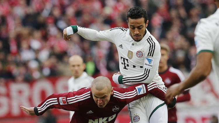 Nuremberg's Adam Hlousek of Czech Republic, left, and Bayern's Thiago Alcantara of Spain challenge for the ball during a match of German first soccer division Bundesliga between 1.FC Nuremberg and Bayern Munich in Nuremberg, Germany, Saturday, Feb. 8, 2014