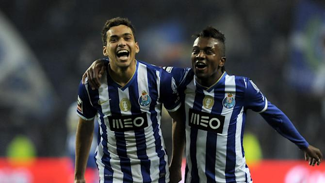 FC Porto's Carlos Eduardo, left, celebrates with Kelvin Oliveira, both from Brazil, after scoring his team third goal against Olhanense in a Portuguese League soccer match at the Dragao Stadium in Porto, Portugal, Friday, Dec. 20, 2013. Carlos Eduardo scored once in Porto's 4-0 victory