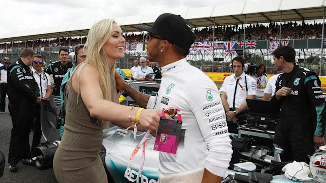 CAR ENT: Skier Lindsey Vonn kisses Mercedes' Lewis Hamilton before the race