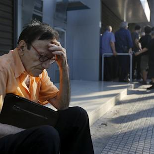 Giorgos, a 77-year-old pensioner from Athens, sits outside a branch of the National Bank of Greece as he waits along with dozens of other pensioners, hoping to get their pensions in Athens