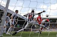 Arsenal's Laurent Koscielny (R) scores during their English Premier League match against West Bromwich Albion at The Hawthorns in West Bromwich, on May 13. Arsenal sealed third place in the league and a guaranteed spot in next season's Champions League with their 3-2 win
