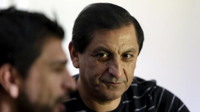 Diaz, head coach of Paraguay's national soccer team, attends an interview with Reuters as his son and assistant Emiliano Diaz looks on, in Asuncion