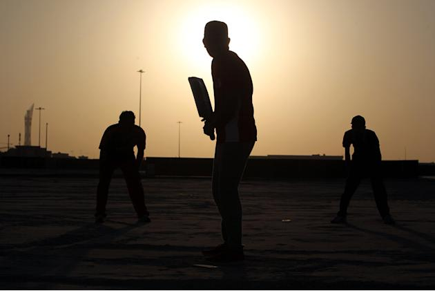 South Asian men play cricket during an excursion in Doha