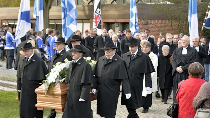 Men carry the coffin with the remains of Adolf Urban, a storied player for soccer club FC Schalke 04 who was killed in Eastern Front fighting in World War II and who is now being reburied in a cemetery in Gelsenkirchen, Germany, Wednesday, Nov. 20, 2013. Urban helped Schalke win five German championships and one German cup before he died 1943 in Russia. His body returned home after 70 years now to a cemetery overlooking the Schalke stadium