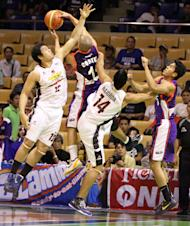 Newly-acquired Mike Cortez grabs the rebound off Dave Marcelo and Leo Najorda. (PBA Images)