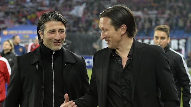 Basel's head coach Murat Yakin, left, and Salzburg's German coach Roger Schmidt talk prior to the Europa League round of sixteen first leg soccer match between Switzerland's FC Basel and Austria's FC Salzburg at the St. Jakob-Park stadium in Basel, Switzerland, on Thursday March 13, 2014