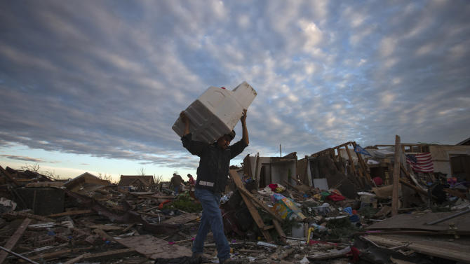 A man carries his belongings through debris after the suburb of Moore, Oklahoma was left devastated by a tornado