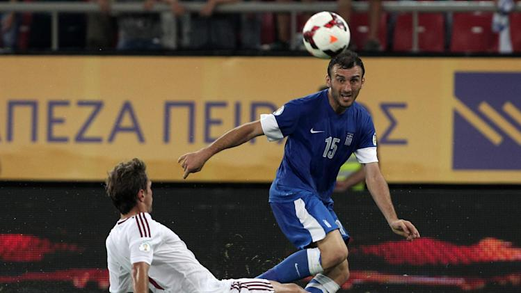 Greece's Vassilis Torosidis, right, and Latvia's Vladislavs Gabovs challenge for the ball during their World Cup Group G qualifying soccer match at the Karaiskaki stadium in Piraeus port, near Athens, on Tuesday, Sept. 10, 2013