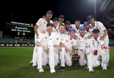 Australia's captain Steve Smith holds the Trans Tasman trophy as he celebrates with his team mates after they defeated New Zealand in the third cricket test match and the series at the Adelaide Ov