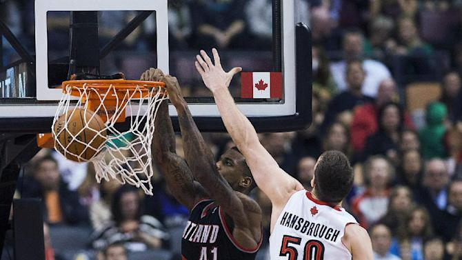 Portland Trail Blazers Thomas Robinson dunks the ball against Toronto Raptors Tyler Handbrough during an NBA basketball game in Toronto on Sunday, Nov. 17, 2013