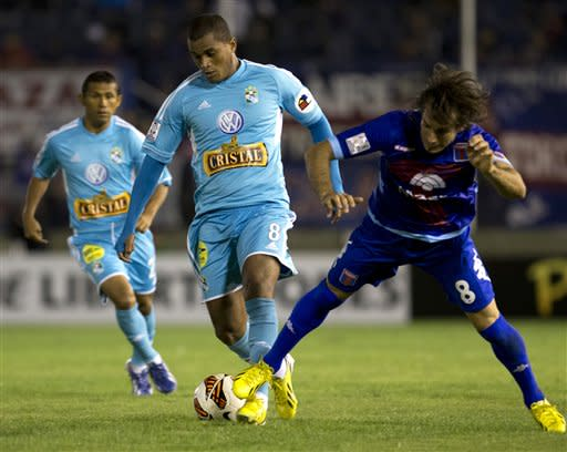 Peru's Sporting Cristal's Nelinho Quina, center, fights for the ball with Argentina's Tigre's Martin Galmarini at a Copa Libertadores soccer match in Buenos Aires, Argentina, Tuesday, April 9, 2013