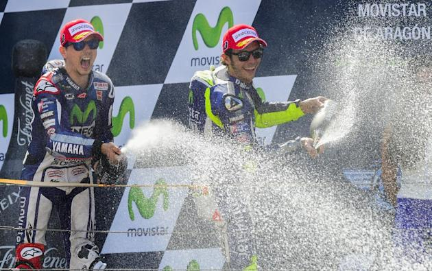 Yamaha Team's Jorge Lorenzo (L) celebrates with teammate Valentino Rossi on the podium after winning the Moto GP race of the Aragon Grand Prix in Alcaniz on September 27, 2015