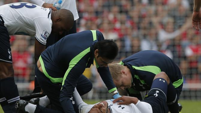 Tottenham Hotspur's Capoue reacts after getting injured during their English Premier League soccer match against Arsenal at the Emirates Stadium in London