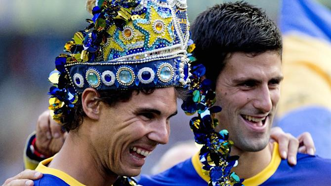 Spain's Rafael Nadal, left, and Serbia's Novak Djokovic pose wearing Boca Juniors' soccer jerseys during an Argentine league match at La Bombonera stadium in Buenos Aires, Argentina, Sunday, Nov. 24, 2013. Nadal is wearing a decorative crown used by Boca Juniors' cheerleaders