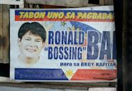 A campaign poster showing an image of Ronaldo Bae, who once ran in local elections for the post of village chief, hangs from a shanty house in Kawit, near Manila, on January 4, 2013. A pregnant woman and four children were among those shot by him on a drug-fuelled rampage