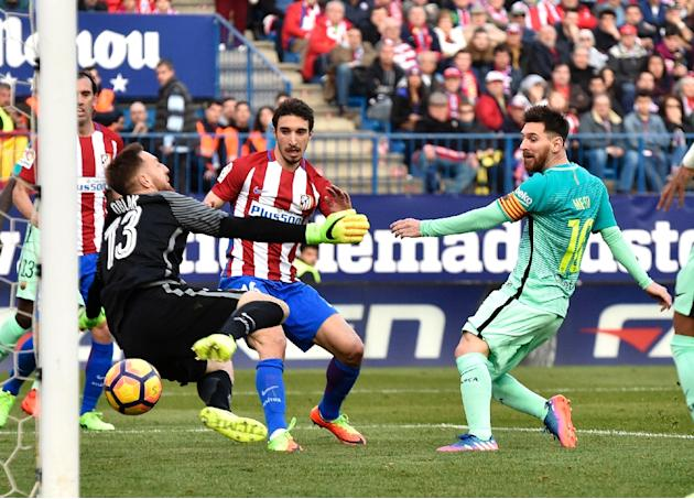 Barcelona's forward Lionel Messi (C) scores a goal during a Spanish league football match against Atletico de Madrid at the Vicente Calderon stadium in Madrid on February 26, 2017