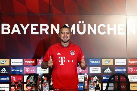 Chile's Vidal, Bayern Munich's new signing, gives thumbs up as he tries out his new jersey at the Allianz Arena in Munich