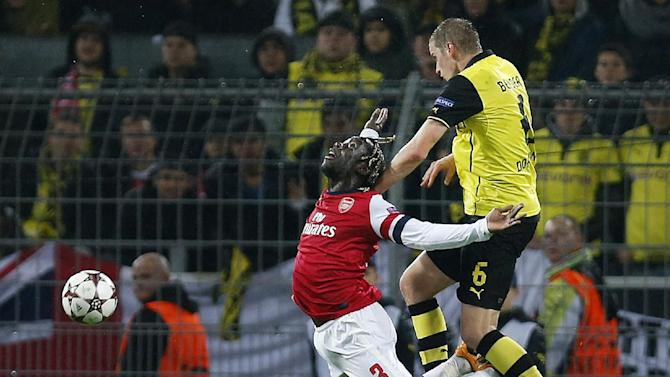 Arsenal's Bacary Sagna, left, is challenged by Dortmund's Sven Bender during the Champions League group F soccer match between Borussia Dortmund and Arsenal FC in Dortmund, Germany, Wednesday,Nov.6,2013
