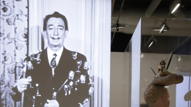 "In this photo taken Monday Nov. 19, 2012, the 'Telephone aphrodisiaque, 1938', by Spanish artist Salvador Dali (1904-1989) is displayed in front of a screen showing an interview of the artist during the presentation to the press of the exhibition ""Dali"" at the Centre Pompidou modern art museum, in Paris. A major retrospective of Salvador Dali in Paris aims to rewrite the art history books, reconciling for the first time the last decades of his life _ when he was accused of money-making self-publicity through numerous television appearances _ with his earlier, respected Surrealist period. (AP Photo/Francois Mori)"