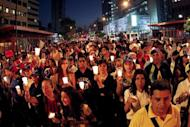 Opposition supporters hold candles as they take part in a rally against Nicolas Maduro's government in Caracas April 10, 2014. REUTERS/Christian Veron