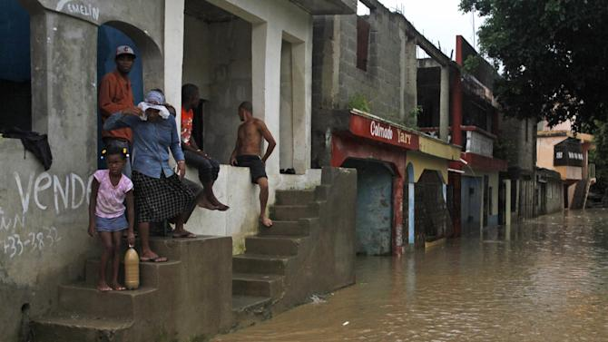 Residents stand above a flooded street in the Cristo Redentor, or Christ Redeemer, neighborhood in Santo Domingo, Dominican Republic, Wednesday, July 10, 2013. Tropical Storm Chantal was downgraded Wednesday to a tropical wave as its scattered clouds drifted quickly westward toward Jamaica. But heavy rains from the weakened system continued to drench parts of Haiti and the Dominican Republic and force the evacuation of thousands from flood-prone areas. (AP Photo)