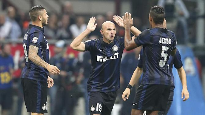Inter Milan Argentine midfielder Esteban Cambiasso, center, celebrates with his teammates forward Mauro Icardi, left, of Argentina, and Brazilian defender Juan Jesus after scoring during the Serie A soccer match between Inter Milan and Fiorentina at the San Siro stadium in Milan, Italy, Thursday, Sept. 26, 2013