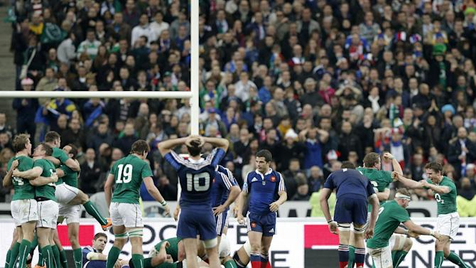 Ireland's rugby team players, in green, celebrate after defeating France and winning the Six Nations Rugby Union tournament at the stade de France stadium, in Saint Denis, outside Paris, Saturday, March 15, 2014